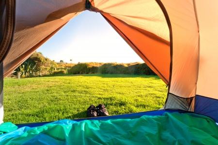 Blick aus der offenen Zelteingang auf der gr�nen Wiese und Wald in Morgensonne Lizenzfreie Bilder