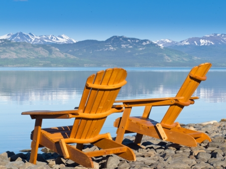 yukon: Two empty wooden Adirondack chairs or Muskoka deckchairs on stony shore overlooking scenic calm Lake Laberge, Yukon Territory, Canada, with snowcapped mountains in the distance Stock Photo