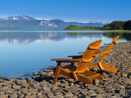 Twee lege houten Adirondack stoelen of Muskoka ligstoelen op steenachtige kust met uitzicht op mooie rustige Lake Laberge, Yukon Territory, Canada, met sneeuw bedekte bergen in de verte