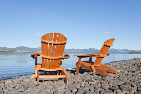 muskoka: Two empty wooden Adirondack chairs or Muskoka deckchairs on stony shore overlooking scenic calm Lake Laberge, Yukon Territory, Canada, with snowcapped mountains in the distance Stock Photo