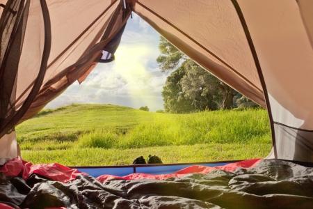 Camping natuur uitzicht op weelderige groene landschap van binnenuit een tent met slaapzakken neergelegd op de vloer