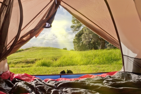 Campsite nature view of lush green countryside from inside a tent with sleeping bags laid out on the floor 免版税图像
