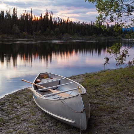 Canoe and paddles beached on shore of beautiful Teslin River in the remote wilderness of Yukon Territory, Canada, the river surface reflecting delicate sunset colors
