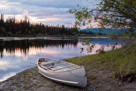 Kano en peddels aan land van mooie Teslin rivier in de afgelegen wildernis van Yukon Territory, Canada, de rivier de oppervlakte als gevolg van delicate zonsondergang kleuren