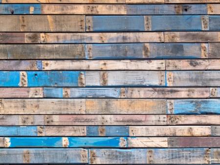Achtergrond textuur patroon van houten planken verweerde met grungy resten van blauwe verf die de gevelbeplating van een buitenspiegel gebouw muur