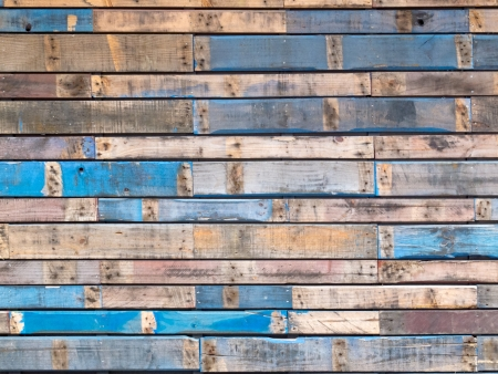 Background texture pattern of weathered wooden planks with grungy remnants of blue paint forming the siding of an exterior building wall