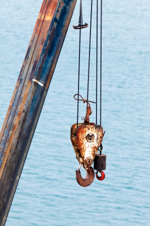 Two different sized battered and rusted hooks and cables of crane for hoisting or lifting heavy loads in harbor against blurry ocean background photo
