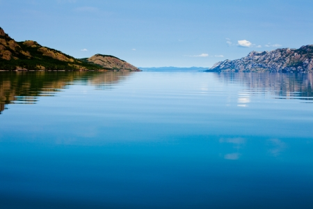 Wide expanse of mirror like calm water surface of huge Lake Laberge, Yukon Territory, Canada, on beautiful summer day Stock Photo
