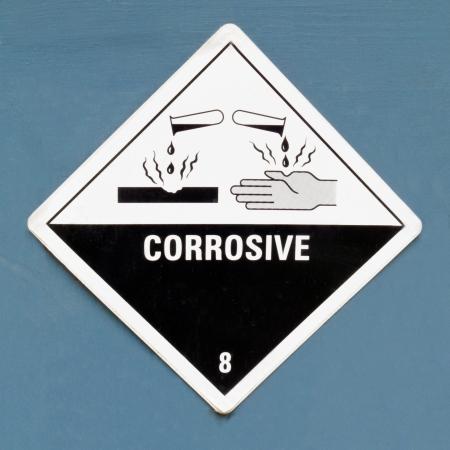 Bijtend, vernietigt op levende weefsels kunnen contact, gevaarsymbool of waarschuwing teken op een geverfde muur waarschuwing niet op de huid bloot te stellen aan stof Stockfoto