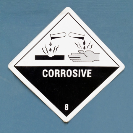 hazardous: Corrosive, destroys living tissue on contact, hazard symbol or warning sign on a painted wall warning not to expose skin to substance