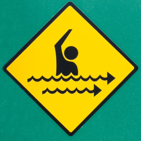 currents: Dangerous rip current hazard symbol warning sign on wall painted green warning of seaward rip currents that can take swimmers out into the ocean