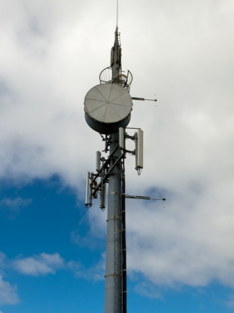 Metal tower with mobile cell phone telecommunications antennas against cloudy blue sky with copyspace