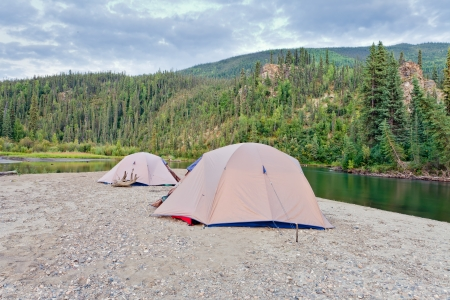 Two tents pitched on a sand bar alongside McQuesten River, Yukon Territory, Canada, in remote boreal forest wilderness