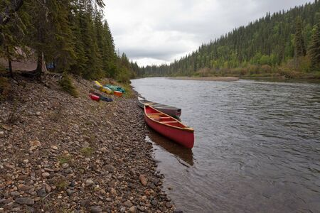 boreal: Tent camp in boreal forest and canoes on paddle river trip on McQuesten River, Yukon Territory, Canada