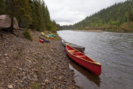 Tent camp in boreal forest and canoes on paddle river trip on McQuesten River, Yukon Territory, Canada photo