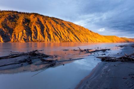 erosion: Eroded clay cliff river bank at Yukon River, Yukon Territory, Canada, near Dawson City glowing in orange light of summer sunset sun Stock Photo