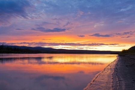 yukon: Beautiful sunset over wilderness of Yukon River, Yukon Territory, Canada, near Dawson City forming a northern riverscape.