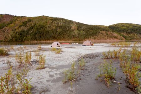 boreal: Beached canoes and two tents pitched on a sand bar alongside Yukon River, Yukon Territory, Canada, in remote boreal forest wilderness Stock Photo
