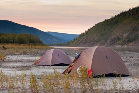 Two tents pitched on a sand bar alongside Yukon River, Yukon Territory, Canada, in remote boreal forest wilderness photo