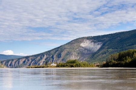 yukon: View of goldrush town of Dawson City and Moosehide Slide on hillside behind seen from Yukon River, Yukon Territory, Canada