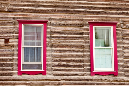 Architectural background of sash windows with colourful red frames in exterior facade of a log building photo