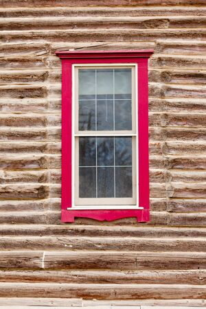 Architectural background of sash window with colourful red frame in exterior facade of a log building Stock Photo - 15661506