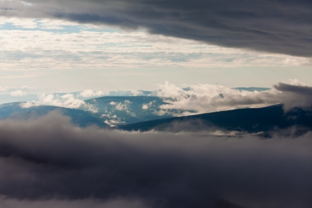billow: Clouds billowing over and between hills and mountains nature landscape.