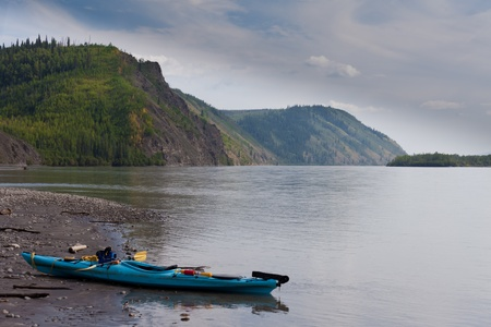 beached: Kayak beached on the shore of Yukon River near Dawson City, Yukon Territory, Canada, during a journey of exploration and adventure Stock Photo