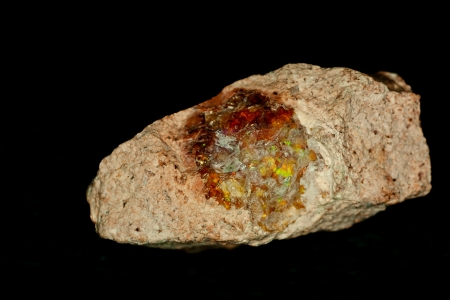 mineralized: Raw Opal, national gemstone of Australia, isolated on black is a mineraloid gel deposited at relatively low temperature, birthstone for October and starstone associated with Libra and Scorpio