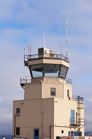 air traffic: Small airport air traffic control tower with huge glass windows and antennas mounted on roof Stock Photo