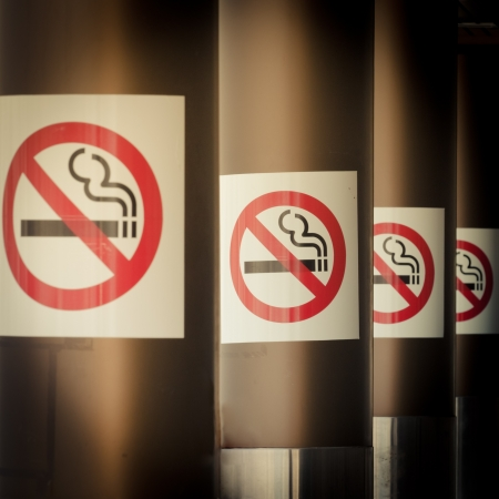 Moble photography lo-fi styled image of series of four No Smoking signs mounted on columns with diminishing perspective for a healthy smoke free environment photo