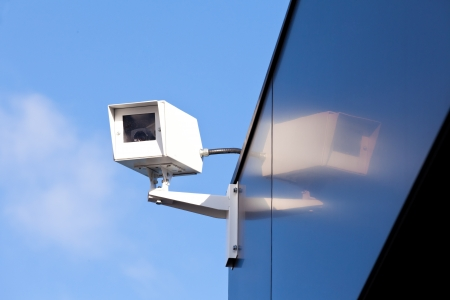Surveillance security camera mounted at and mirrored on external shiny facade of building for safety and security causing privacy issues Stock Photo - 17092792