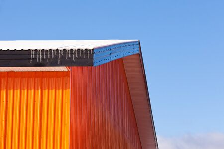 Orange metal sheet siding warehouse construction in winter with snow and ice on roof