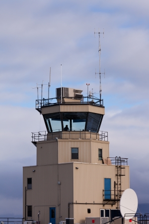 Small airport air traffic control tower with silhouette of man behind huge glass windows monitoring the airfield photo