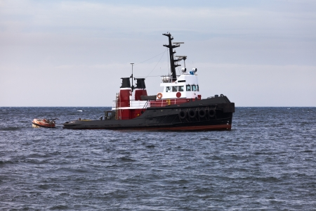 tug boat: Powerful tug-boat with high bows for pushing or pulling cargo or marine vessels floating in wait on calm ocean at anchor Stock Photo