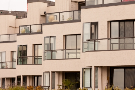 units: External facade of contemporary residential apartment block development with large glass windows and balconies for every unit.