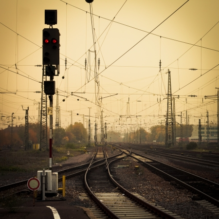 railway track: Moble photography lo-fi styled image of confusing urban railway tracks with ines and overhead cables and a red signal light at foggy dusk