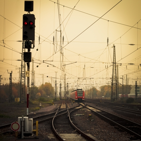commuters: Moble photography lo-fi styled image of a red commuter train on an urban railway track with confusing lines and overhead cables and a red signal light