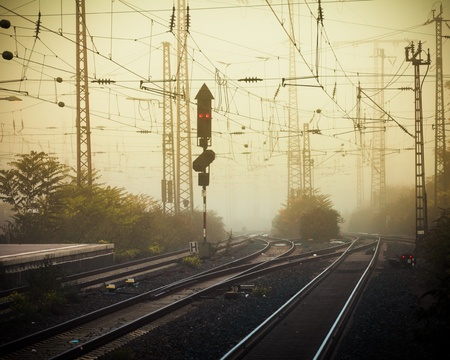 junctions: Moble photography lo-fi styled image of confusing urban railway tracks with ines and overhead cables and a red signal light at foggy dusk