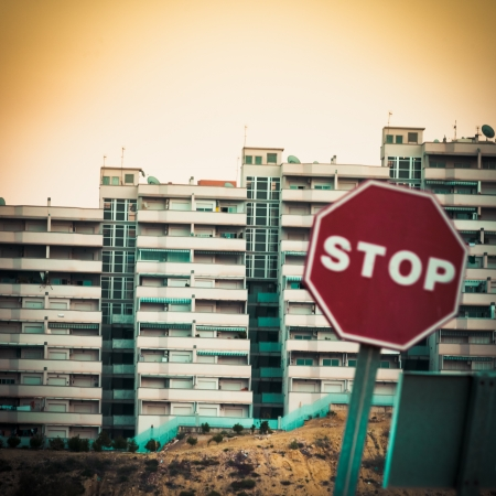 gentrification: Moble photography lo-fi styled image of blurry stop sign in front of huge concrete high-density apartment complex Stock Photo
