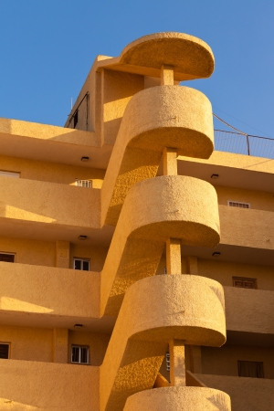 architectural feature: Exterior spiral staircase apartement block architectural feature on multistorey colorful yellow-orange modern condo unit in sunshine of Spain