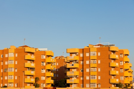 apartment: Group of multistorey colorful yellow-orange modern architecture apartment blocks in sunshine against a clear blue sky with copyspace