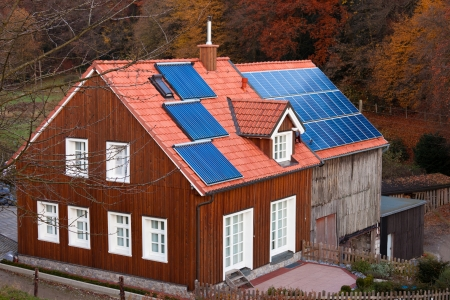 Historic farm house with modern solar electric and solar heating system on large roof. Stock Photo - 17092798