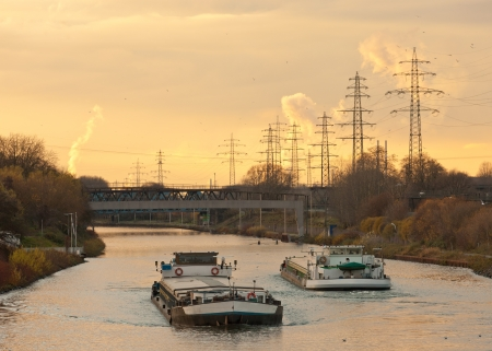 inland: Inland waterway vessels on a busy channel in industrial area near a bridge under the warm glow of an evening sunset