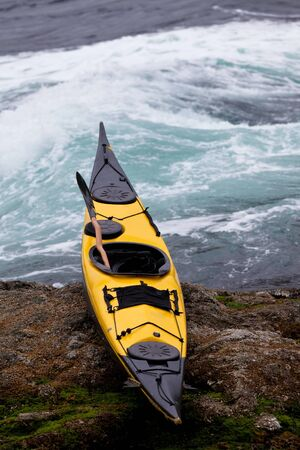 beached: Colourful yellow sea kayak and paddle beached on a rocky ledge alongside whitewater tidal rapids Stock Photo