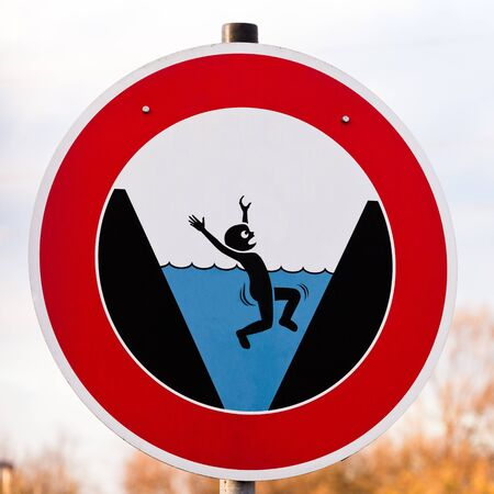 pictorial: Circular hazard sign warning of danger of drowning with a pictorial illustration showing a person trapped by surroundings drowning in blue water