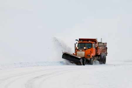Snow plough truck clearing road after whiteout winter snowstorm blizzard for vehicle access photo