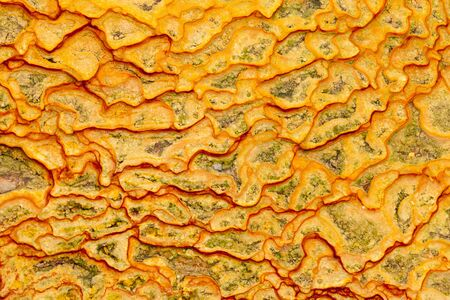 iron oxide: Background texture pattern of natural iron oxide rich yellow-orange mineral sediment deposit from water