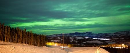 Northern Lights or Aurora borealis or polar lights illuminating overcast sky over snowy winter road landscape Stock Photo - 17840805