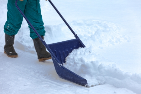 Manual snow removal from driveway using a snow scoop by person wearing boots